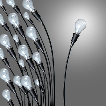 new path: Independent idea business concept and new creative thinking and individual creativity symbol or going it alone breaking away from a group as a a bunch of lightbulbs leaning on one side and an individual light setting a new path. Stock Photo