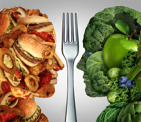 fast eat: Nutrition decision concept and diet choices dilemma between healthy good fresh fruit and vegetables or greasy cholesterol rich fast food shaped as a human head divided by a fork as a symbol for trying to decide what to eat. Stock Photo