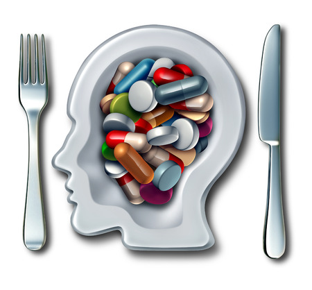 droga: Medicamentos cerebrales y el concepto de la medicina de la neurociencia como un plato con cuchillo y tenedor en forma de una cabeza humana con medicamentos como las p�ldoras y c�psulas como una droga inteligente s�mbolo de la salud mental para la investigaci�n en terapia nueva neurolog�a. Foto de archivo
