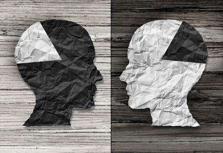 mixed marriage: Ethnic equality concept and racial justice symbol as a black and white crumpled paper shaped as a human head on old rustic wood background with contrasting tones as a metaphor for social race issues.