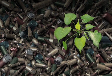 After war concept as a background of rustic bullets and amunition from weapons with a green sapling tree sprouting out from the metal as a surreal global peace issue metaphor for hope and reconciliation after a bloody conflict.