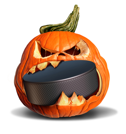 Hockey in autumn concept as a pumpkin jack o lantern biting into a hard black ice puck as a symbol for halloween sports and fall and winter sporting events on a white background. Zdjęcie Seryjne