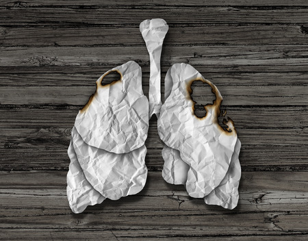Human lung cancer concept or illness and losing human lungs health care symbol as a decline in respiratory function caused by a tumor disease as the organ made of crumpled white paper with burnt holes on a wood background.