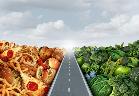 junk: Diet lifestyle concept or nutrition decision symbol and food choices dilemma between healthy good fresh fruit and vegetables or greasy cholesterol rich fast food with a road or path between leading to a light.