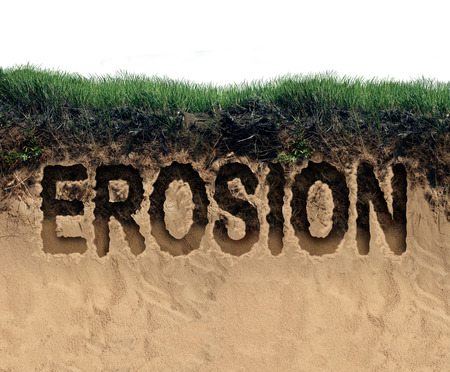erosion: Erosion concept as a coastal cliff of top soil and sand eroding away as an environmental damage symbol for land loss due to the forces of nature or global warming crisis.