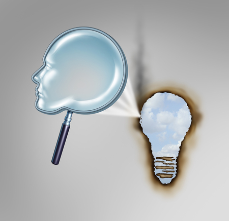 Human creativity concept as a magnifying glass shaped as a head profile creating a hot beam of light burning a hole in paper in the shape of a light bulb as a metaphor for creative thinker.