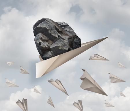 Kracht van motivatie zakelijke succes concept als een papieren vliegtuig vervoeren van een heavy rock met een groep van falende origami vliegtuigen als een metafoor voor de kracht van de bepaling. Stockfoto
