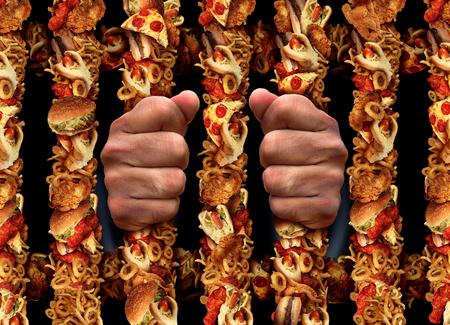 Junk dipendenza da cibo e mangiare concetto di stile di vita malsano con aprison barre sagomate fatte di hamburger di pollo fritte e hot dog elaborati prodotti di carne e patatine fritte come un simbolo dei pericoli di essere intrappolati da grasso zucchero e sale.