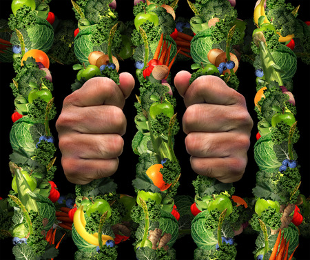 Healthy eating obsession  concept and addicted to health food symbol or or orthorexia nervosa as an extreme eating habit of consuming only certain foods as human hands holding prison bars from a jail cell made of fruits and vegetables. Imagens