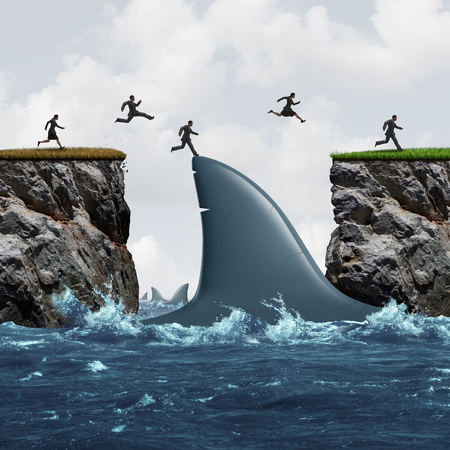 Profit from risk business concept as a group of businesspeople taking advantage of challenging market conditions as a businessman and businesswoman jumping on a shark fin as a bridge to success and opportunity metaphor. Фото со стока
