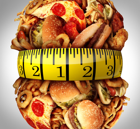 measure: Obesity waistline diet concept as a group of unhealthy fast food as hamburgers,fries and hot dogs bulging out as a fat stomach with a tape measure wrapped around the greasy food.