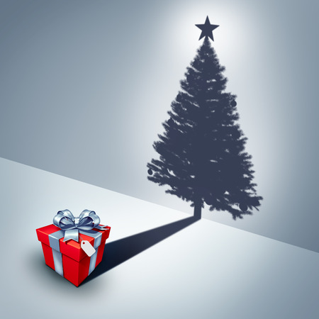 christmas spirit: Holiday present dream concept as a gift casting a shadow shaped as a decorated christmas tree as a surreal winter celebration metaphor for the spirit of giving and xmas celebration symbol. Stock Photo