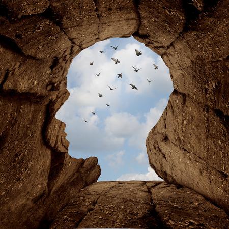 コンセプト: 形の空高くを飛んでいる鳥たちのグループと新しい人生のメタファーと成功動機シンボルとして人間の頭の上に開口部をもつ岩の崖と想像力と発見