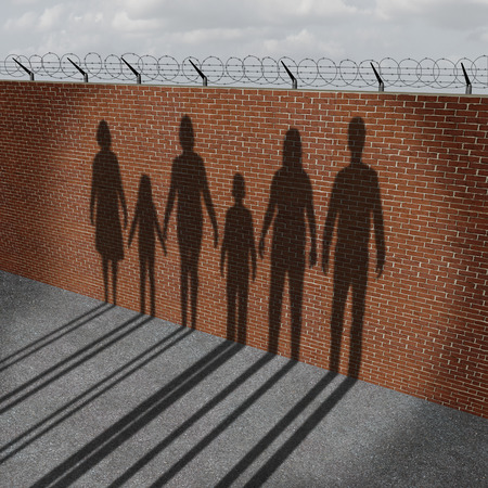 Immigration people on a border wall as a social issue about refugees or illegal immigrants crisis with the cast shadow of a group of migrating women men and children.