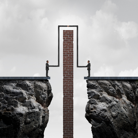surmount: Making a deal overcoming obstacles to an agreement as a business concept of strong flexible partnership success as two people on isolated cliffs stretching their arms to go around a brick wall for a handshake connection. Stock Photo