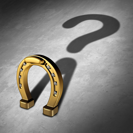 lucky charm: Chance question and luck questions as a horseshoe icon or horse shoe odds symbol as a golden metal lucky charm object as a metaphor for fortune and lotto or lottery success uncertainty and prediction risk.
