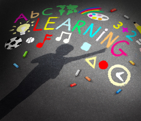 discover: Child learning concept as the shadow of a young student on a schoolyard pavememt with chalk drawings of music math reading and art symbols as a metaphor for childhood creativity and the potential to learn and discover.