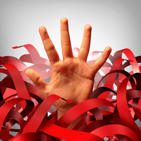 Bureaucratic red tape problem as a human hand tangled in bureaucracy and regulations as a business concept and symbol of government gridlock or corporate regulatory confusion. Stock Photo