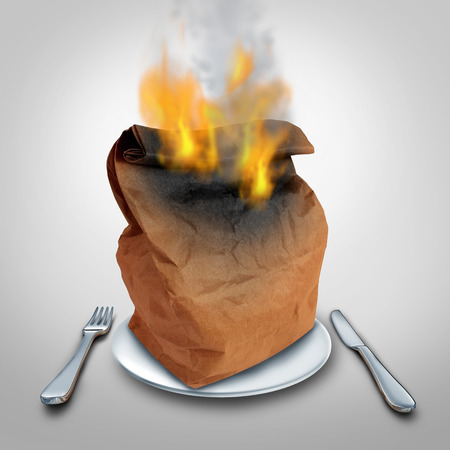 food waste: Burning calories or burn calorie concept and hot lunch idea or food waste symbol as a brown paper lunch bag that is in flames on a plate as an icon for spicy cuisine or contaminated meal problem.