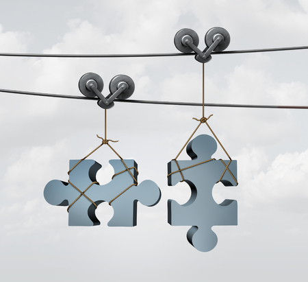 coming together: Connecting puzzle pieces as a merger or merging business concept with two jigsaw objects on two guidance cable wires or zip liner tool aligning and coming together as a partnership.