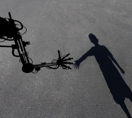 infancia: Tecnología ayudando concepto de los niños como la sombra de un niño intreacting llegar a un brazo de robot asistido por ordenador avanzada como asistente símbolo aprendizaje y la enseñanza o la ciencia de la niñez y el icono de la ingeniería inspiración imaginación.