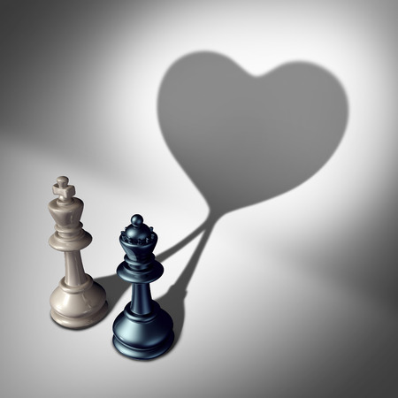 coming together: Couple in love as a valentines day concept as a white king and black queen chess piece casting a united cast shadow coming together in a romantic relationship as a symbol for happy romance and emotional attraction. Stock Photo