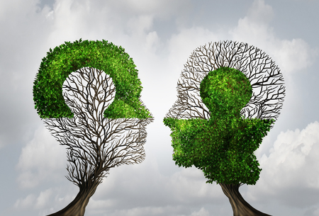 connection: Perfect business partnership as a connecting puzzle shaped as two trees in the form of human heads connecting together to complete each other as a corporate success metaphor for cooperation and agreement as equal partners.