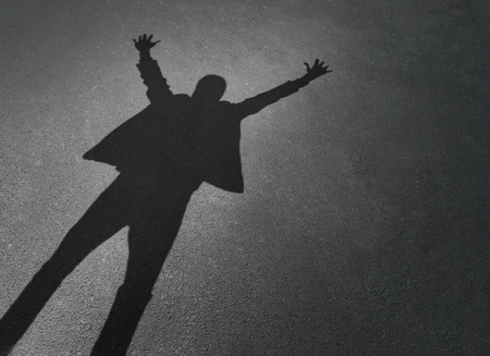 Business person corporate success as a cast shadow of a successful businessman celebrating with arms up in the air on a pavement background as a winning entrepreneur.