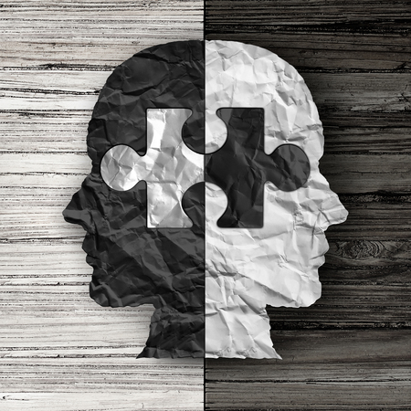 bigotry: Racial ethnic social issue and equality concept or cultural justice symbol as a black and white crumpled paper shaped as a human head on old rustic wood background with a puzzle piece as a metaphor for social race issues.