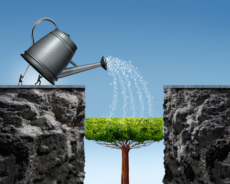 long term: Planning for future success business concept with a businessman and businesswoman lifting a watering can to help a tree grow into a future bridge to achieve the long term goal of crossing to the other side. Stock Photo