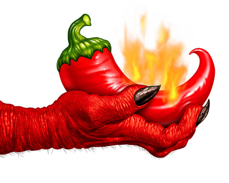 Hot pepper devil hand as a red chili burning in flames being held by a demon hand as a food symbol for spicy seasoning cooking isolated on a white background.