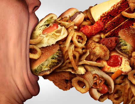 Eating junk food nutrition and dietary health problem concept as a person with a big wide open mouth feasting on an excessive huge group of unhealthy fast food and snacks.