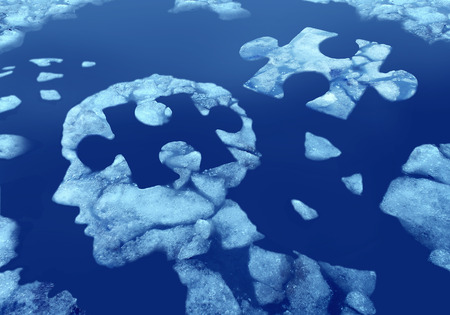 psychiatry: Puzzle head idea and concept as a human face profile made from floating icefloating away in water with a jigsaw piece cut out on a cold blue arctic background as a mental health symbol. Stock Photo