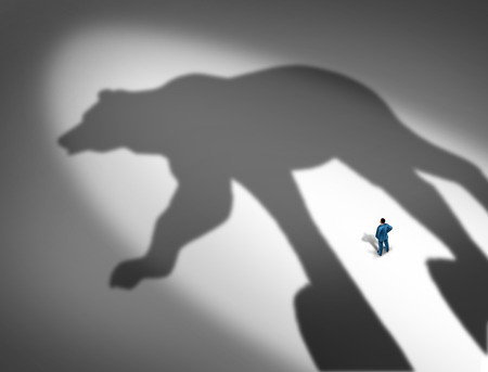 shrinkage: Looming financial crisis and slumping stock market business concept as a businessman standing in front of the cast shadow of a bear as a loss and price decline metaphor. Stock Photo