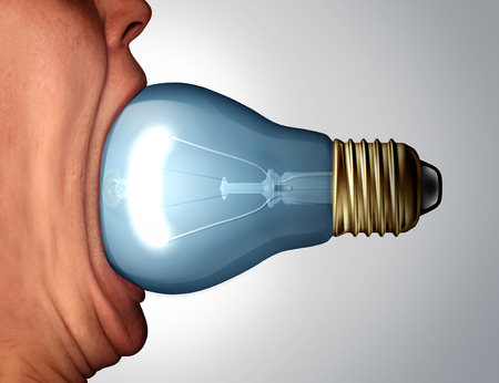 creativity symbol: Creative diet concept as a an open huge human mouth eating a light bulb or lightbulb object as a business communication icon and marketing creativity symbol.