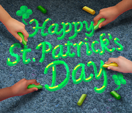 coming together: Happy Saint Patricks day concept as a group of diverse people coming together drawing green St Patrick day text with chalk as a spring time traditional Irish pride celebration symbol. Stock Photo