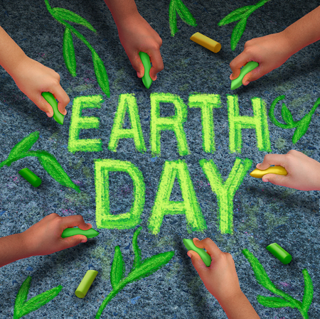 coming together: Earth day and environmental protection symbol as a group of diverse ethnic people coming together drawing text and leaves with green chalk on a pavement floor as a global community collaboration to save the planet.
