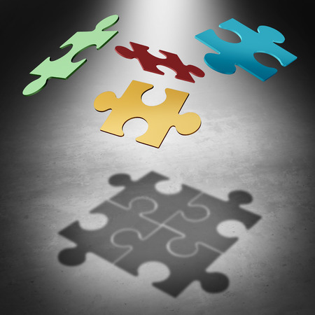 divided: Putting the puzzle together teamwork concept as a business success symbol with four divided pieces of a jigsaw puzzle flying in the air creating a cast shadow that unifies the team as a unity metaphor. Stock Photo