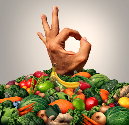 tastes: Delicious healthy food concept as a chef hand emerging out of a mountain of green fruit vegetables nuts and berries as a nutrition metaphor for savory fresh market produce.