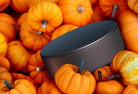 halloween background: Autumn hockey season concept as a group of pumpkins with a black ice puck as a symbol for halloween sports and fall and winter sporting events on a white background.