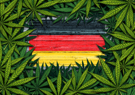 Germany marijuana and German cannabis symbol with the flag on rustic wood with leaves as a border in a 3D illustration style.