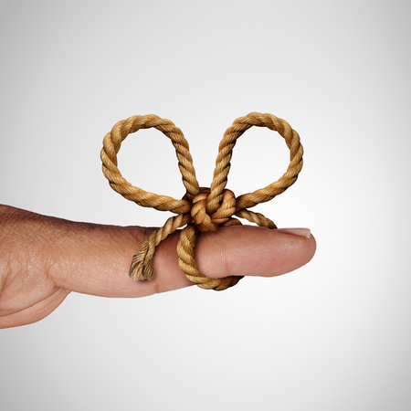 Remember knot and reminder symbol as a string tied on a finger to remind and give attention to a future planned event. Stock Photo
