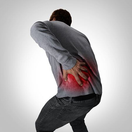 Painful back symptoms and lower spinal pain or backache and painful spine medical concept as a person holding the painful area as a medical concept as a composite image.