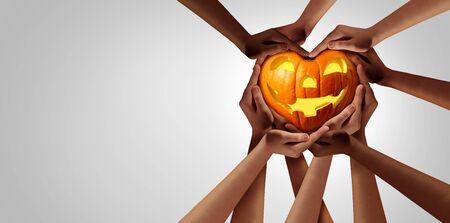 Halloween diversity group and pumpkin shaped as a heart as a jack o lantern seasonal symbol with a group of diverse people holding a happy seasonal gourd. Stock Photo