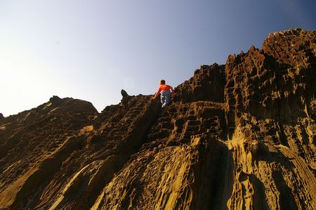 Boy climbing mountain Stock Photo