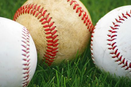 Baseballs in the grass on a baseball field Stock Photo