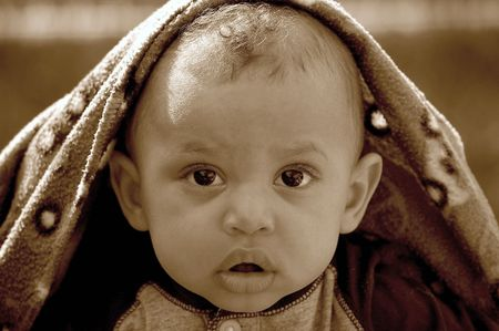 A young child of mixed race peeking out from under a blanket with a surprised look on his face