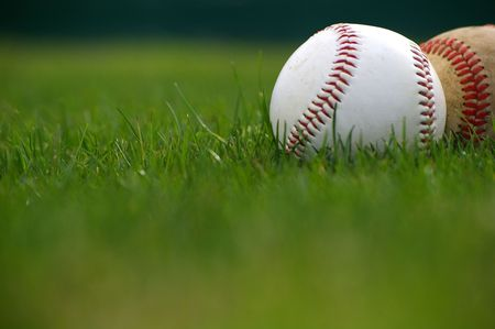 Ground level shot of two baseballs in the grass done with selective focus Stock Photo