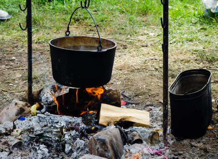 Cooking in a hike in the cauldron hanging over the fire, from the boiler coming white smoke