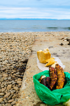 life loaf: Smoked fish  Omul and loaf of bread on the background of Lake Baikal